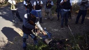 Polícia comunitária mexicana diante de corpo de um membro da quadrilha Cavaleiros Templários no Estado de Michoacán.
