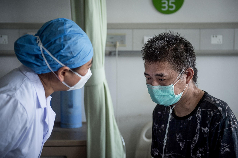 Un médecin chinois s'entrtient avec le dernier patient guéri du Covid-19 dans un hôpital de Wuhan, le 17 juin 2020.