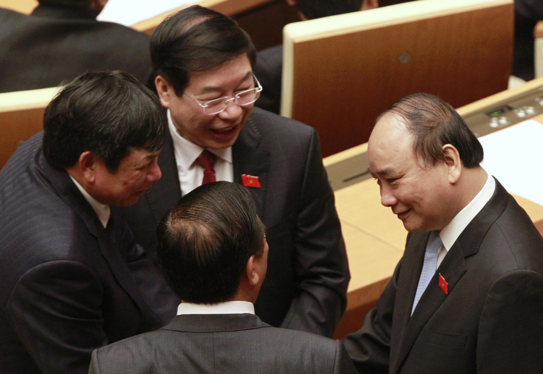 Phó thủ tướng Nguyễn Xuân Phúc (phải) trò chuyện với các đại biểu Quốc hội trong phiên khai mạc tại Hà Nội ngày 21/03/2016.