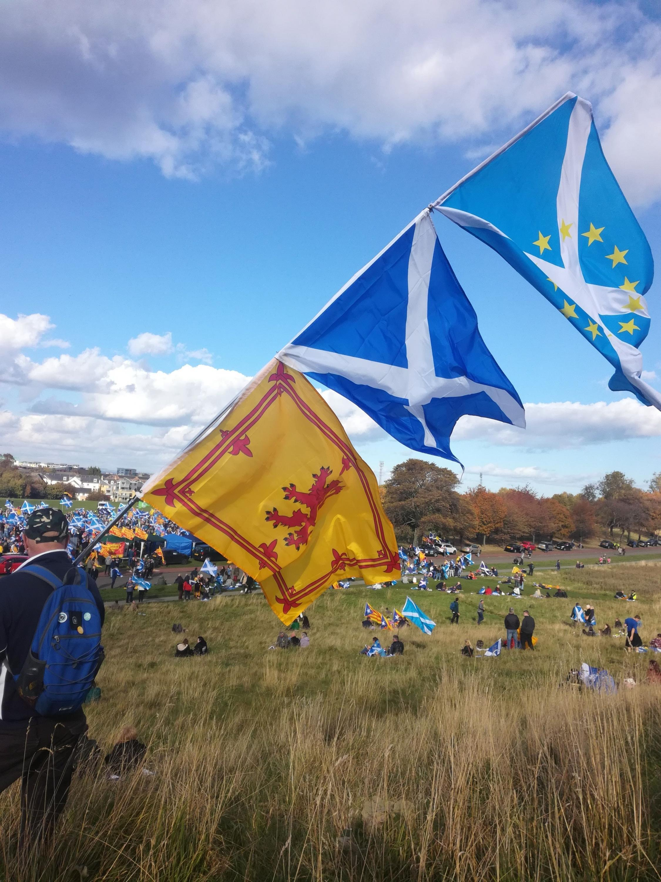 A man carries a pole holding flags of Scotland and the European Union
