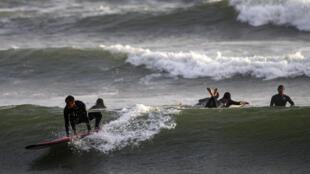 Deportistas practican surf en una playa de Lima, el 22 de octubre de 2020