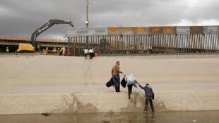 Migrantes del lado mexicano sale de un río hacia las obras del nuevo mureo entre El Paso, Texas, y Ciudad Juárez en México, el 5 de febrero de 2019.