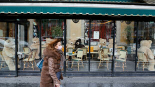 A woman wearing a protective mask walks past the Deux Magots café in central Paris as the French government prepares to announce tougher measures that could include new restrictions in the region around the capital, one of the hardest hit by the current wave of infection of the new coronavirus.