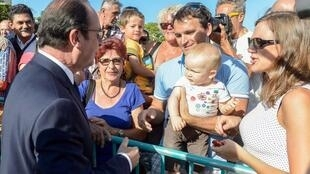 rance's President Francois Hollande (L) talks to lFormer French president Francois Hollande talking to ocal residents following a wreath-laying ceremony at the Memorial Bir Hakeim square in Noumea on November 17, 2014.