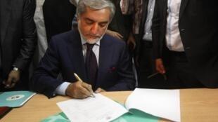 Abdullah Abdullah signe le registre sur lequel il se déclare candidat à l'élection présidentielle afghane, le 1er octobre 2013.