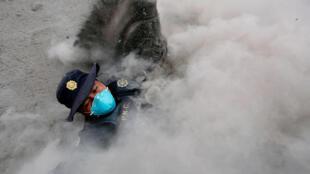 Un oficial de policía tropieza al escapar de un nuevo flujo piroclástico arrojado por el volcán Fuego en la comunidad de San Miguel Los Lotes en Escuintla.