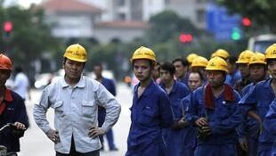 Des travailleurs attendent le bus après leur journée de travail dans le quartier financier de Shanghai, le 8 juillet 2013.