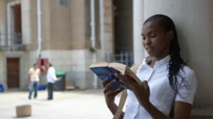 Une jeune fille lisant un livre sur un campus sud-africain.