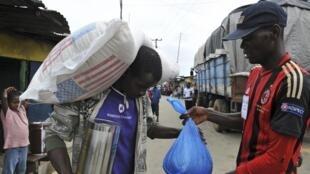 Em Monróvia, capital da Libéria, população em quarentena recebe alimento do Programa Mundial de Alimentos, da ONU.