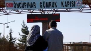 兩名敘利亞人抵達與土耳其接壤的邊境城市基里斯(KILIS)後,期待自己的親友能夠順利抵達此地。(2016年2月8日)
