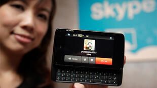 A woman displays a new Nokia N900 smartphone which can make Skype calls during a news conference in Taipei