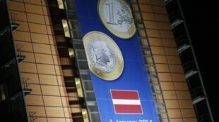 Biểu ngữ mang hình đồng euro và cờ Latvia, tại trụ sở UB Châu Âu, Bruxelles, nhân Thượng đỉnh Liên Hiệp Châu Âu, 20/12/2013