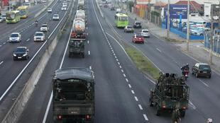 Caminhões do Exército escoltam caminhão-tanque de entrega de combustíveis em rodovia perto de Porto Alegre.