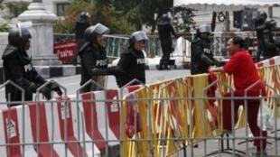 Một người phe Áo Đỏ đang trò chuyện với các nhân viên cảnh sát đứng gác trước tòa nhà chính phủ, ngày 31/3/2010.