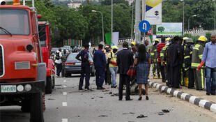 People gather at the scene of one of the bomb blasts in Abuja, 1 October 2010.