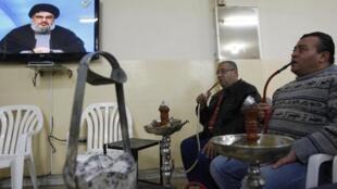 Des hommes écoutent dans un café à Sidon, le 16 janvier 2011, la retransmission télévisée du discours du chef du Hezbollah, Hassan Nasrallah.