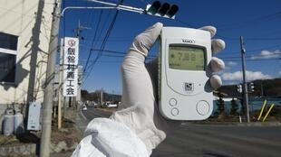 A Greenpeace member holds up a Geiger counter to monitor radioactivity levels at Iitate village, 40 kms from Fukushima, on Monda