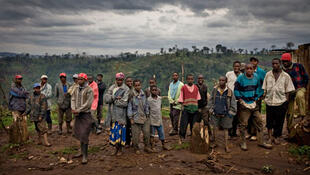 Kenyans who live on disputed land at the Mau forest stand by the roadside at a makeshift village