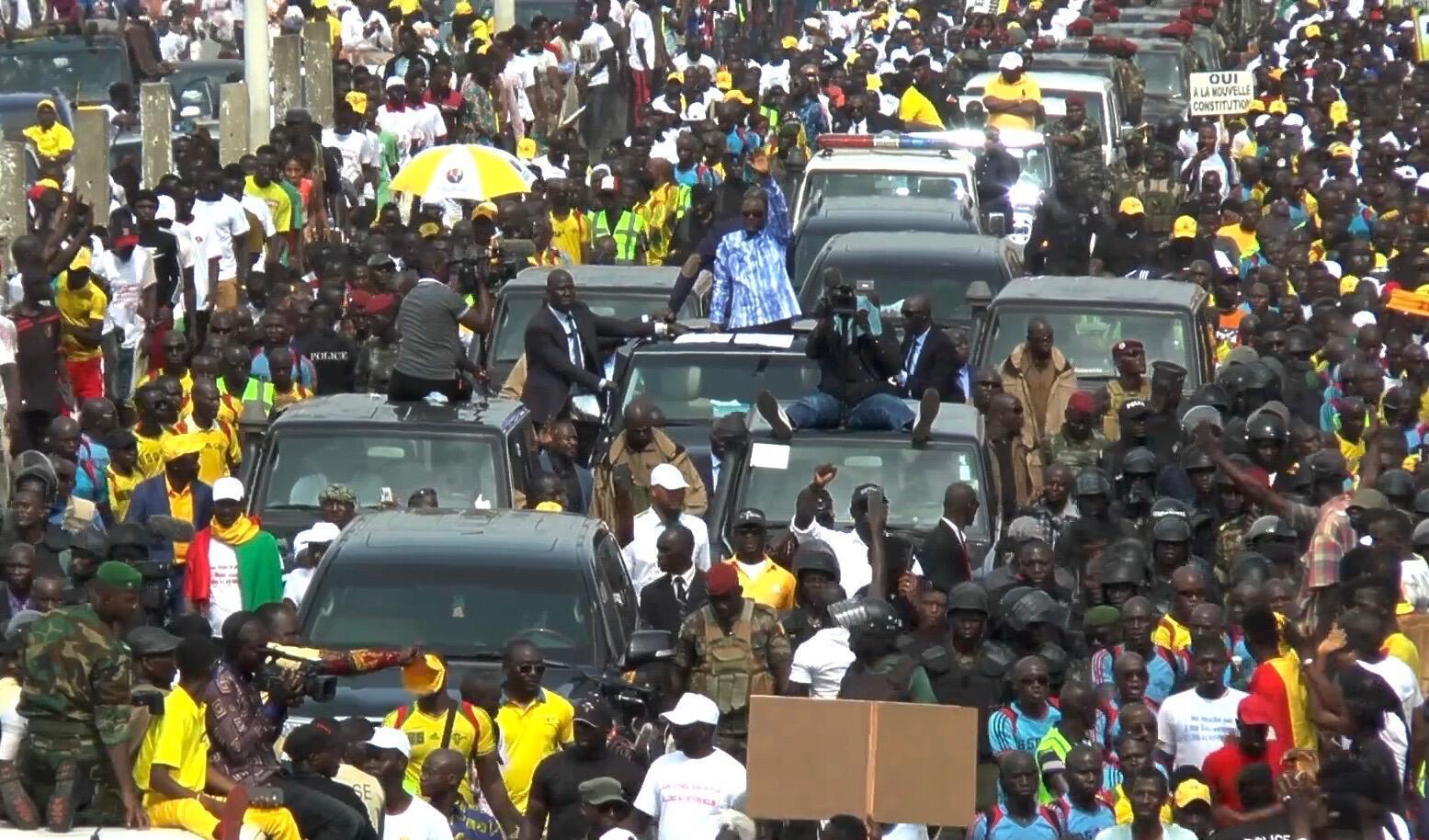 Le président guinéen Alpha Condé, en chemise bleue au milieu des militants venus le soutenir, lors d'une manifestation le 31 octobre 2019.