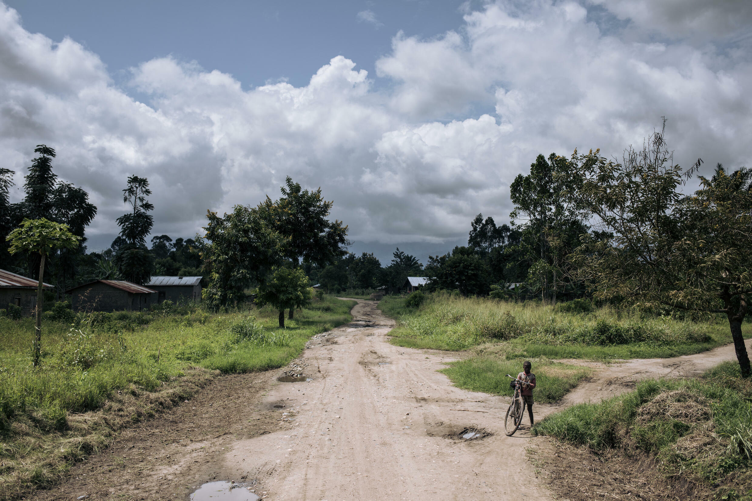 Deserted: A boy rides a bicycle at the entrance to the town Mutwanga. Many residents have fled their homes because of attacks