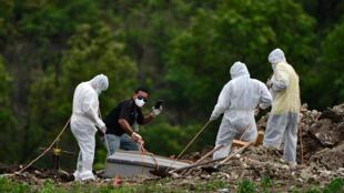 Un hombre filma con un teléfono móvil el entierro de una víctima de COVID-19 en las afueras de Tegucigalpa, el 7 de junio de 2020 en medio de la pandemia de coronavirus que avanza en Honduras.