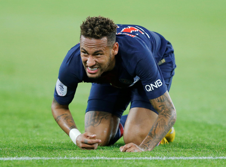 Neymar se ajoelha no chão após ser atingido por um zagueiro do Caen.