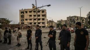 Askari polisi mbele ya jengo la vikosi vya usalama lililoharibiwa na bomu lililotegwa katika gari katika mji wa Shubra kaskazini mwa Cairo Agosti 20, 2015.