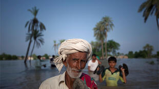 Flood victims wade through water in Punjab province.