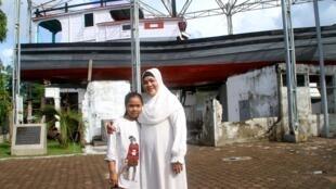 Fauziah et sa fille devant Le Bateau sur la Maison, à Aceh.