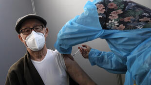 A man receives Pfizer's COVID-19 vaccine at a vaccination site in Paris, Saturday, March 6, 2021_AP_Christophe Ena