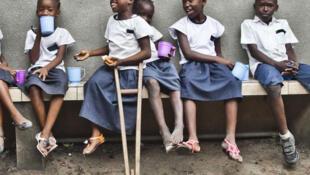 Grâce (C), 8 ans, amputée à cause d'une infection puis appreillée et desormais scolarisée. (Ici en RDC).