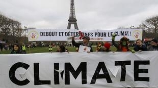 "Environmentalists hold a banner which reads, 'Standing and Determined for the Climate"" at a protest near the Eiffel Tower in Paris, France, as the World Climate Change Conference 2015 (COP21) in the French capital last December"