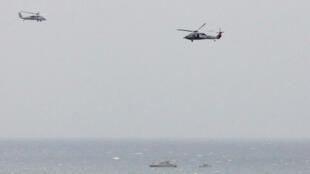 ទូកឆ្មាំការពាររបស់អ៊ីរ៉ង់ នៅជិតនាវាផ្ទុកយន្តរបស់អាមេរិក USS George H. W. Bush នៅឯច្រកសមុទ្រអកមូ ខណៈដែលឧទ្ធម្ភាគចក្រកងទ័ពជើងទឹកអាមេរិកហោះក្បែរនោះ កាលពីថ្ងៃទី២១ មីនា ឆ្នាំ២០១៧។
