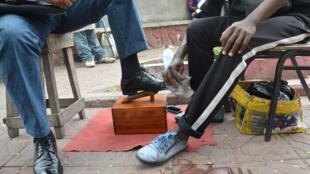 Un cireur de chaussures à Kinshasa, en RDC.