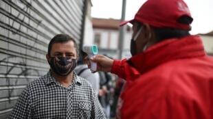 Un employé contrôle la température d'un client avant d'entrer dans un magasin, le 17 juin 2020 à Bogota
