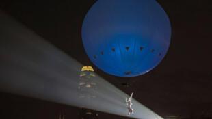 Une danseuse du spectacle «The dream engine : Héliosphere» suspendue à un énorme ballon gonflé à l'hélium.