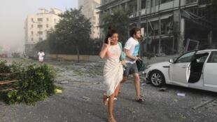 Des gens courent se mettent à l'abri suite aux explosions dans la zone portuaire de Beyrouth, au Liban, le 4 août 2020.
