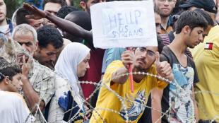 Migrantes sirios frente a la frontera entre Grecia y Macedonia.