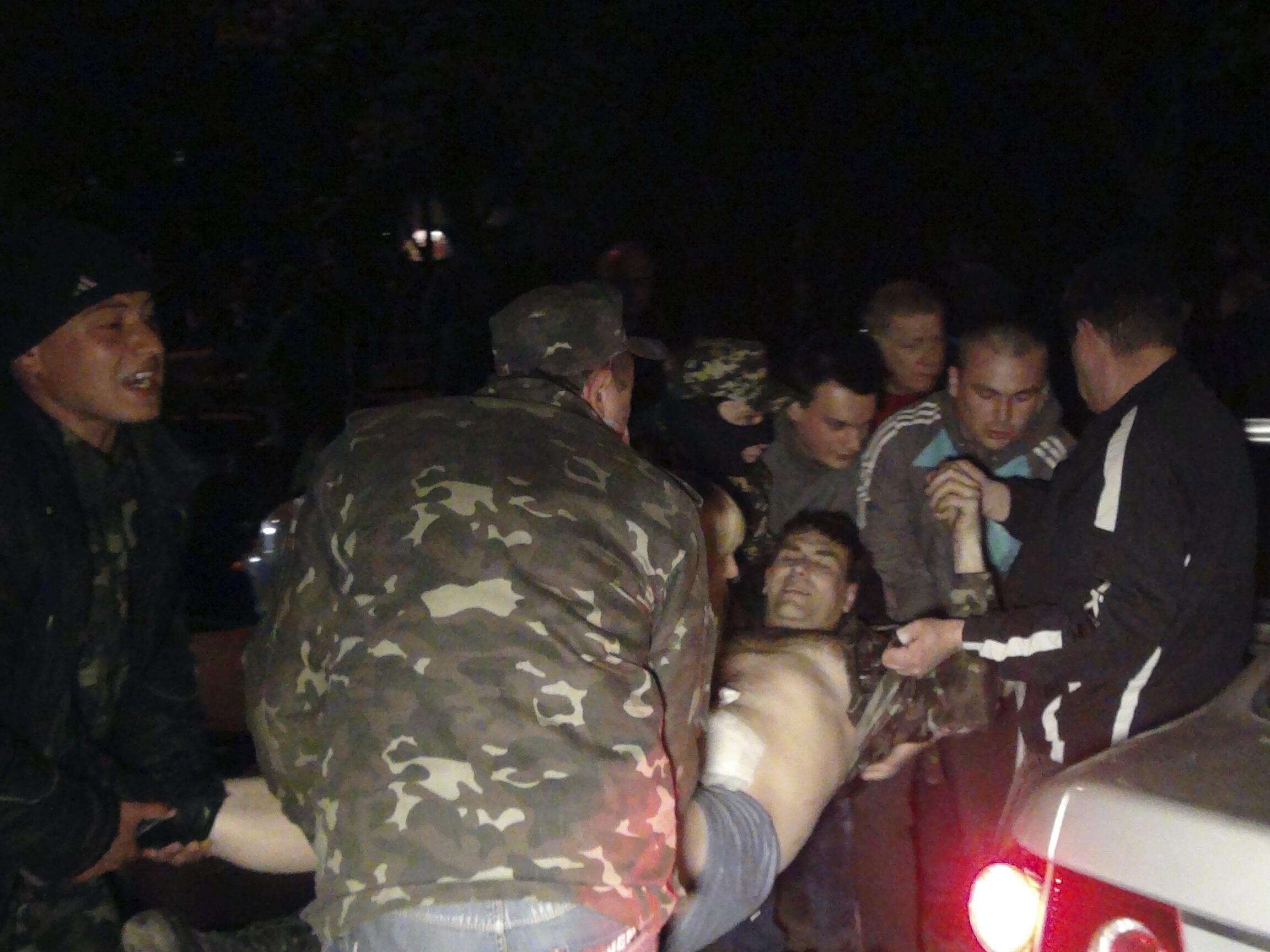Люди переносят тело убитого при нападении на военую базу в Мариуполе, 16 апреля 2014.