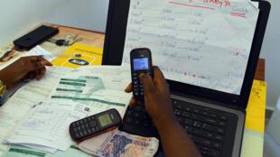 Une hôtesse d'Orange Money règle une facture par paiement téléphonique, en mai 2015.
