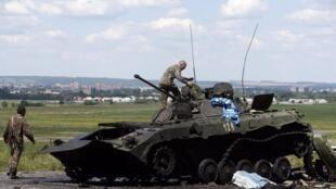 Украинский военный проверяет подбитый бронетранспортер на КПП украинской армии под Славянском, 5 июля 2014 г.