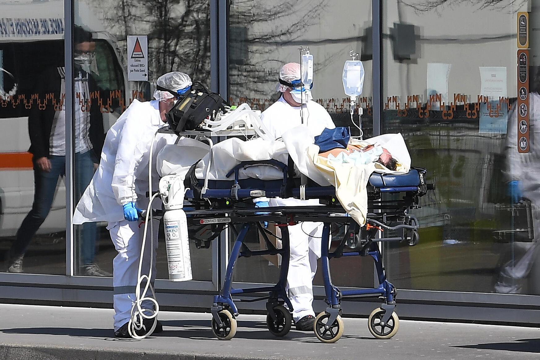 Un paciente con ayuda respiratoria es conducido al hospital Universitario de Estrasburgo por miembros del servicio de urgencias vestidos con trajes protectores el 16 de marzo de 2020 en la ciudad francesa