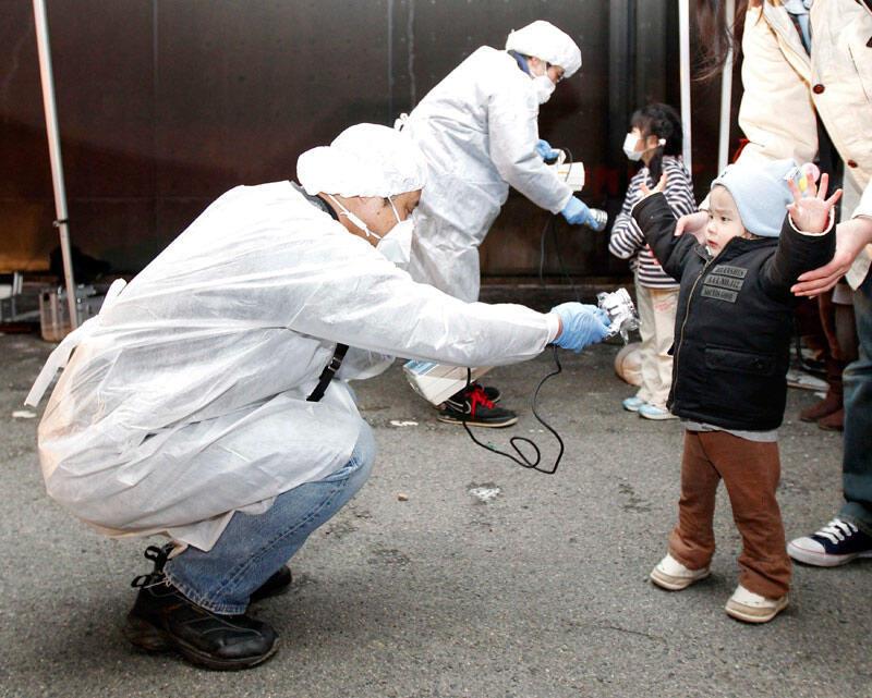 Des officiels vérifient les signes de radiation sur les enfants du secteur d'évacuation proche de la centrale nucléaire de Fukushima Daini à Koriyama, le 13 mars 2011.