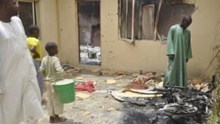 Des badauds devant le bâtiment où Edgar Fritz Raupach, l'otage allemand aux mains d'Aqmi, a été tué au cours d'une tentative de sauvetage par l'armée nigériane à Kano, le 31 mai 2012.