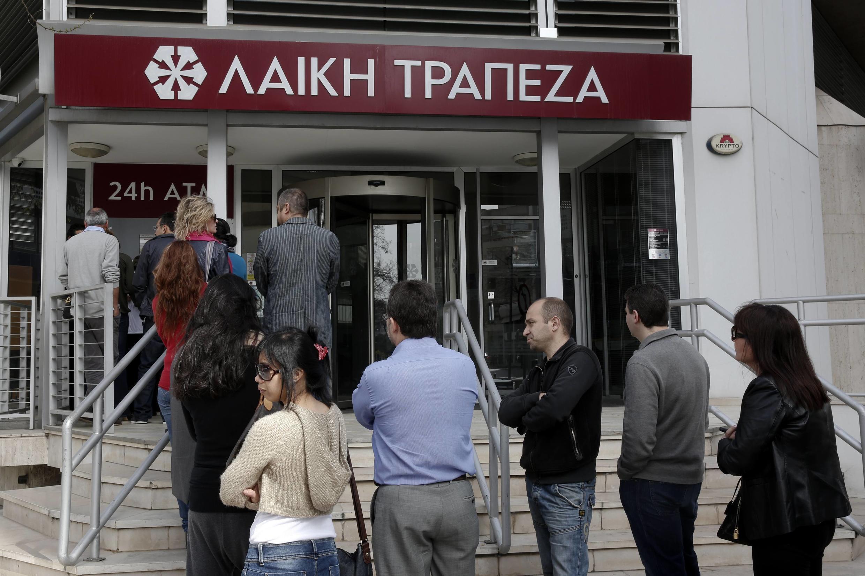 File d'attente devant un distributeur de billets de la Banque Laïki, menacée de disparition par l'accord de sauvetage de Chypre, le 21 mars 2013.