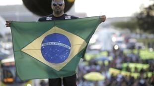 Policial levanta a bandeira brasileira durante passeata da polícia civil contra os gastos públicos na Copa do Mundo,  realizada nesta quarta-feira (21), na Esplanada dos Ministérios, em Brasília.