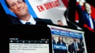 Les estimations des Français lors de l'élection présidentielle française sont partagées sur Twitter et affichées sur les écrans à Lavigny, en Suisse, le 22 avril 2012.