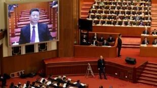 Le président chinois Xi Jinping sur un écran géant, lors de la séance d'ouverture de la Conférence consultative politique du peuple chinois (CCPPC) au Grand Palais du Peuple à Beijing, en Chine, le 3 mars 2019.