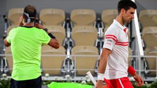 El serbio Novak Djokovic (derecha) pasa junto al español Rafael Nadal durante su partido de semifinales individuales masculinos en el torneo de Roland Garros 2021, en París, el 11 de junio de 2021.