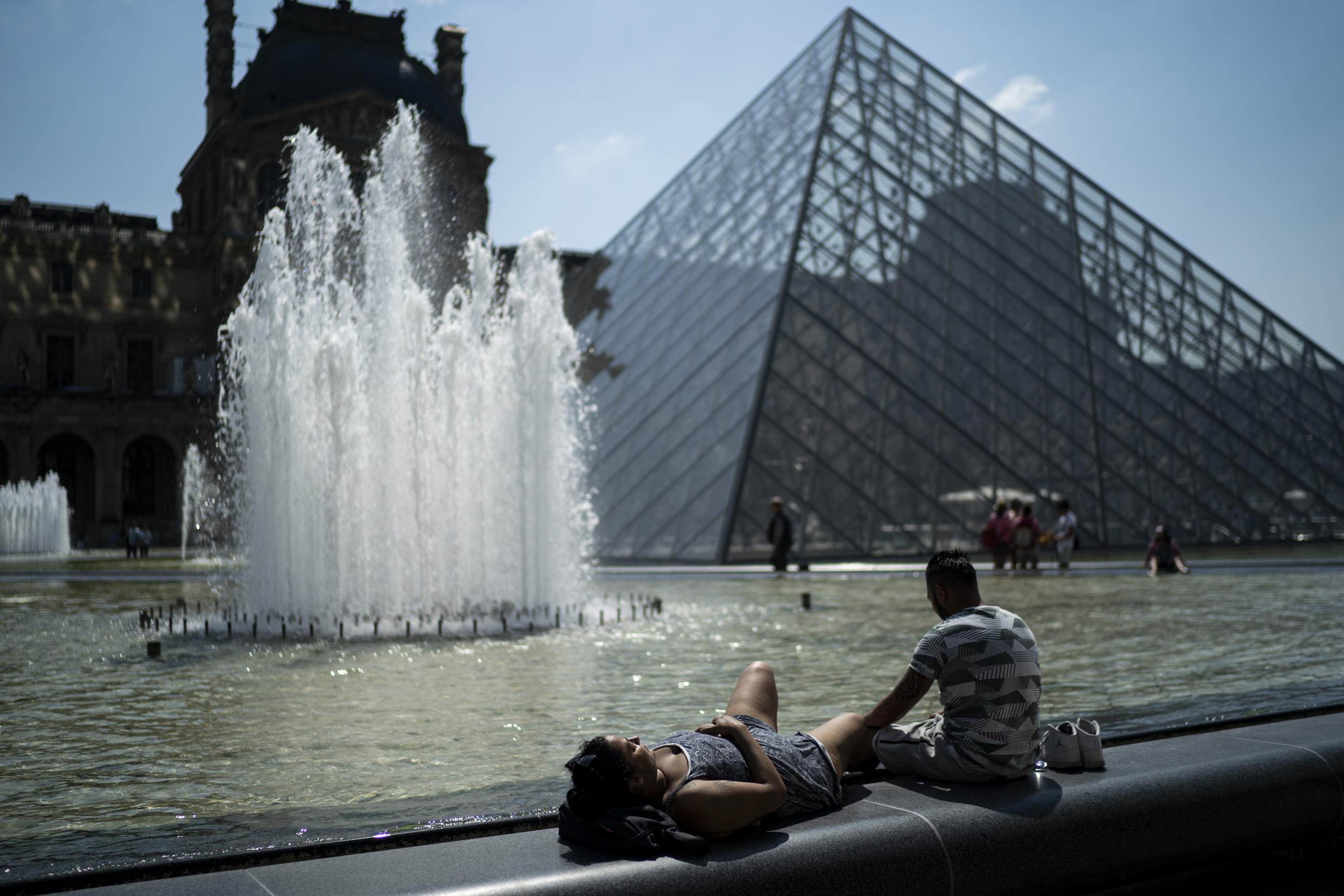 Visitors relax at the entrance of the Louvre museum in Paris, where temperatures were expected to reach 32 degrees Celsius on Monday.